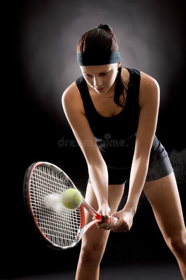 与球拍的黑色网球妇女命中球 库存图片