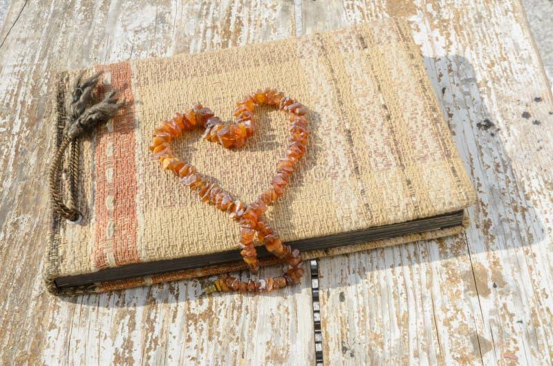 与琥珀色的项链心脏的老象册 免版税库存照片