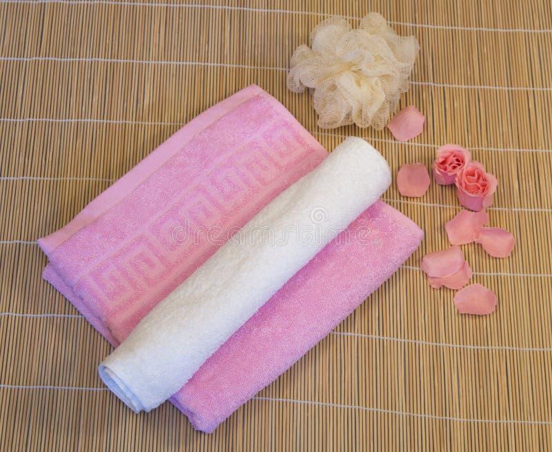与瓣的桃红色,白色毛巾在竹席子 免版税库存图片