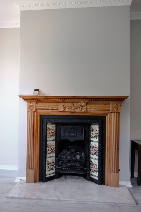 与瓦片修剪的维多利亚女王时代的黑生铁壁炉在木杉木周围和大理石壁炉边 免版税库存图片