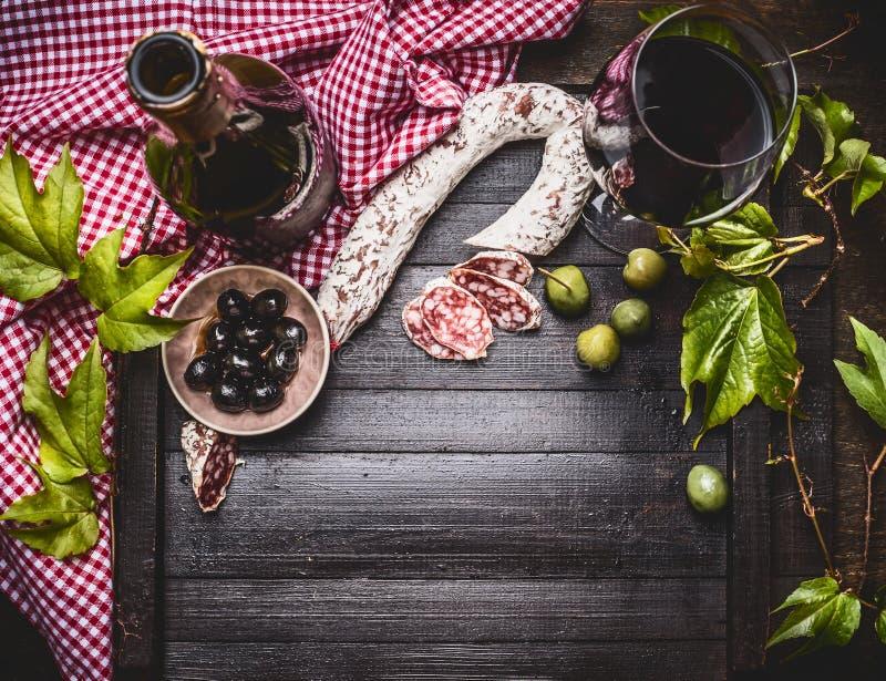 与瓶和一杯的意大利食物静物画红葡萄酒、橄榄和香肠在黑暗的土气背景,顶视图 图库摄影