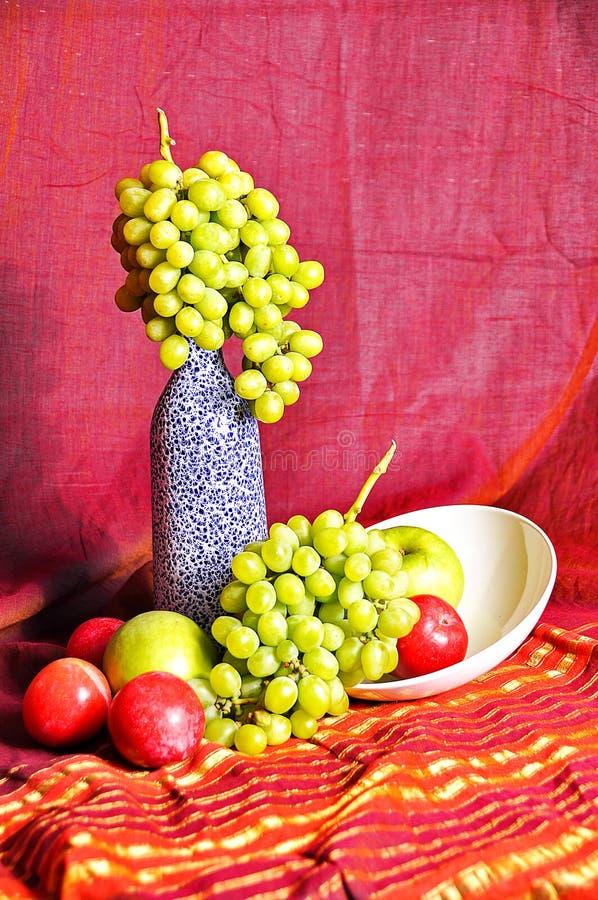 与瓶和果子的静物画:桃子、苹果和葡萄在东方样式 库存图片