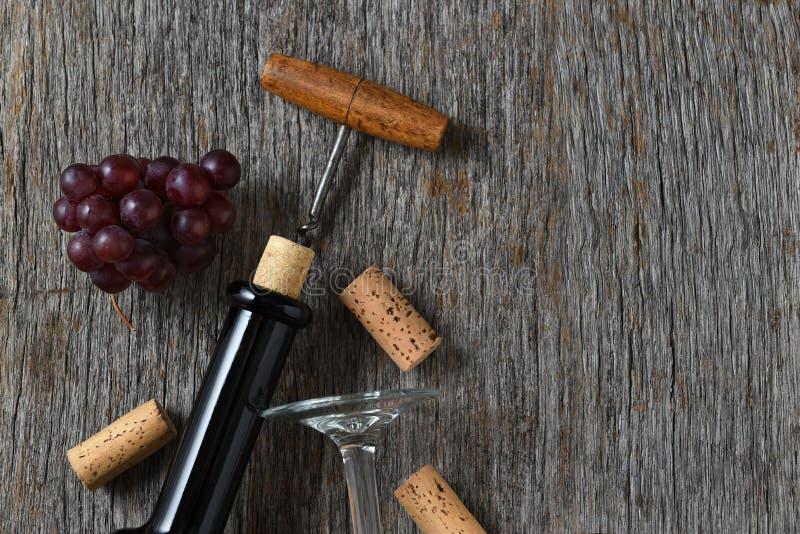 与瓶拔塞螺旋,在一张土气木桌上的葡萄的酒静物画 免版税库存图片