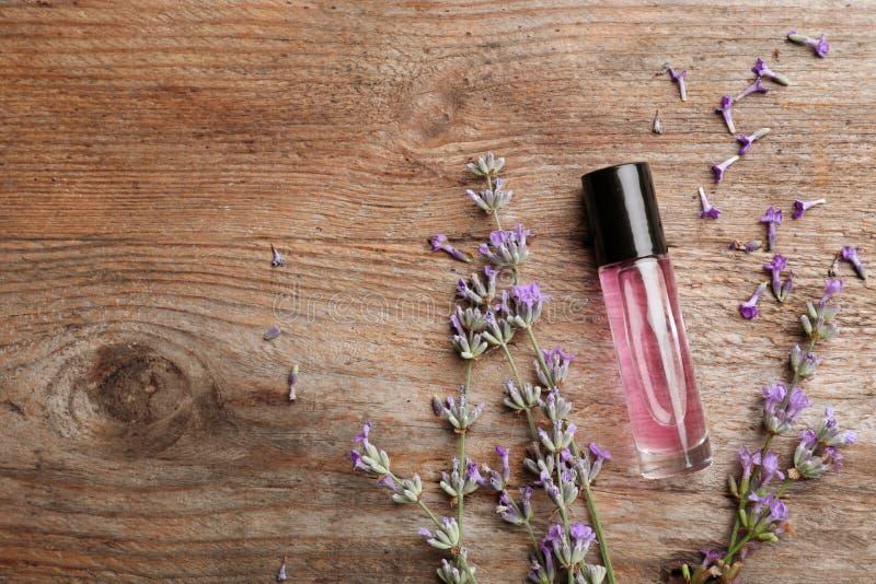 与瓶的平的被放置的构成自然在木背景的淡紫色精油 库存图片