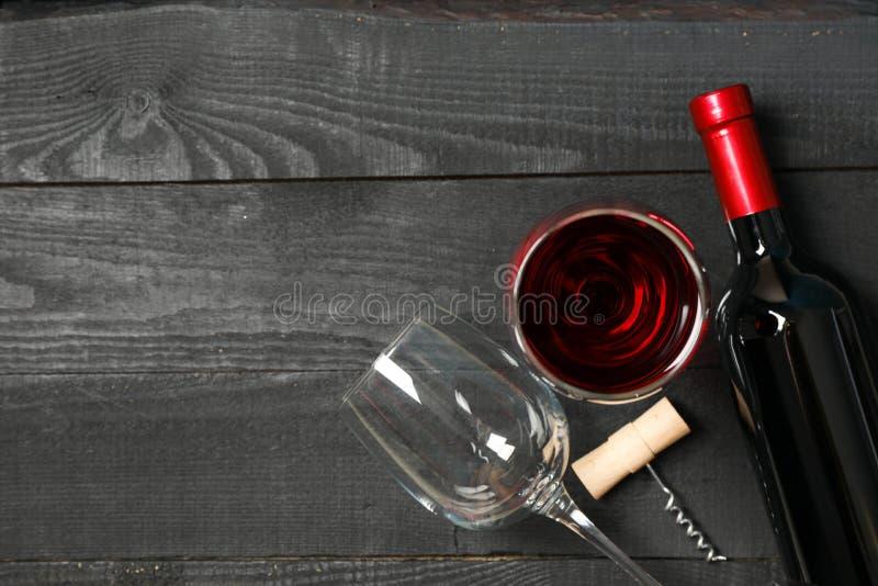与瓶的平的被放置的构成酒、玻璃和拔塞螺旋在木背景 库存照片