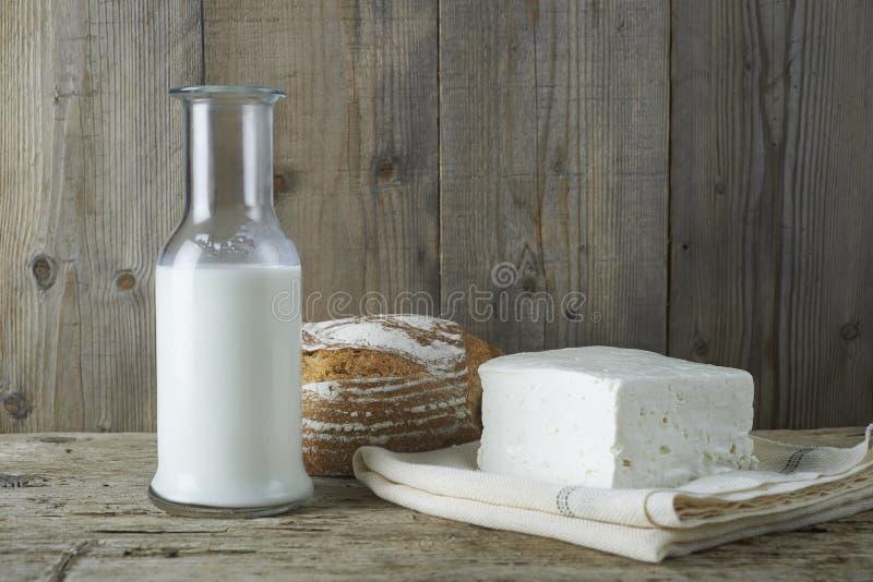 与瓶的新鲜的希腊白软干酪牛奶和面包 库存照片