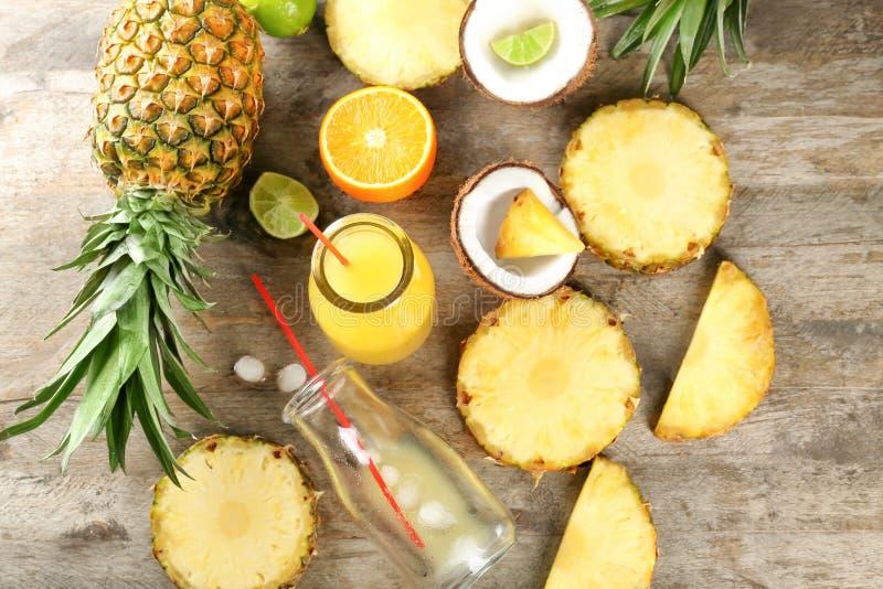 与瓶的构成菠萝汁和果子在木背景 免版税库存图片