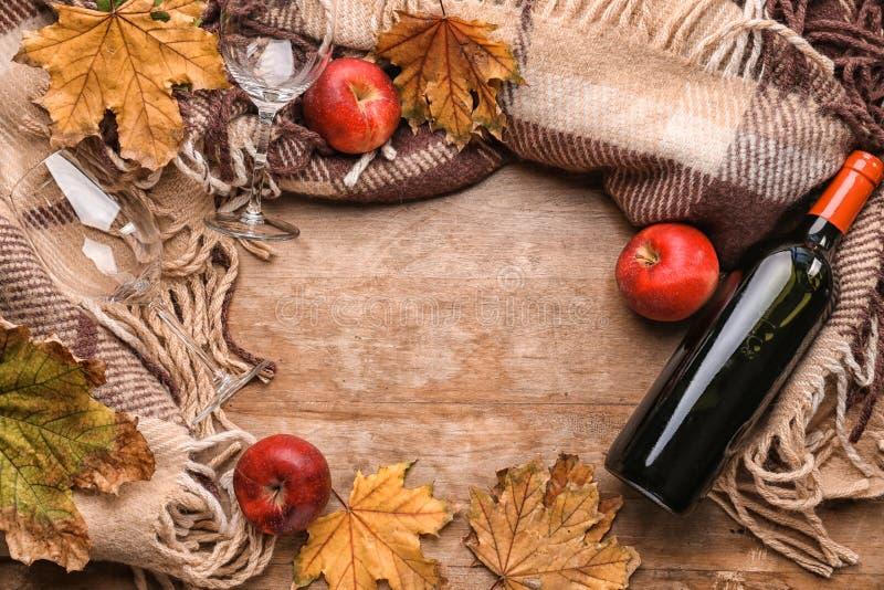 与瓶的构成酒、温暖的格子花呢披肩和秋叶在木背景 库存照片