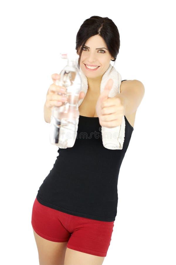 与瓶的美丽的体育运动女孩赞许水 免版税库存照片
