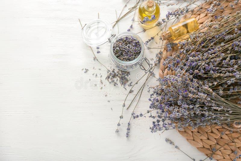 与瓶的美丽的淡紫色花在白色桌上的精油 免版税库存图片