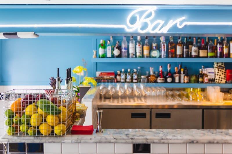 与瓶的逆酒吧在背景和水果篮中在大理石柜台在前景 库存照片