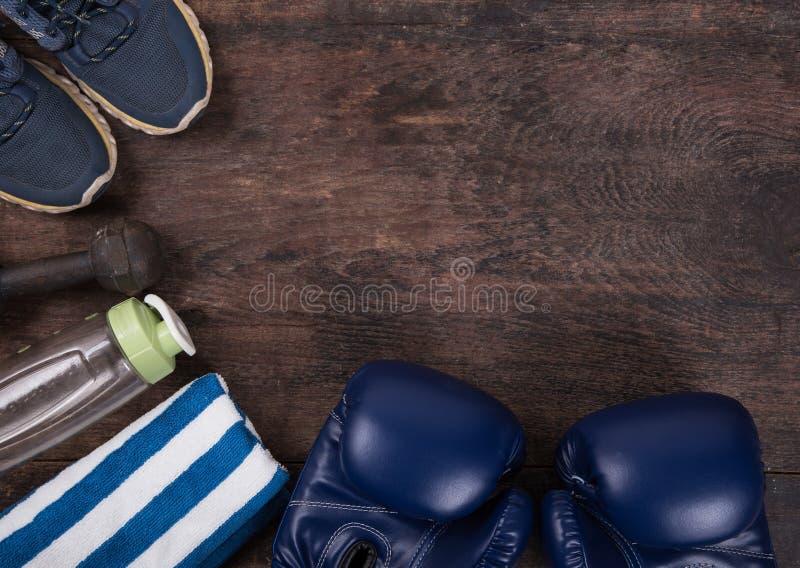与瓶装水、鞋子、毛巾、耳机和拳击手套的健身 免版税库存照片
