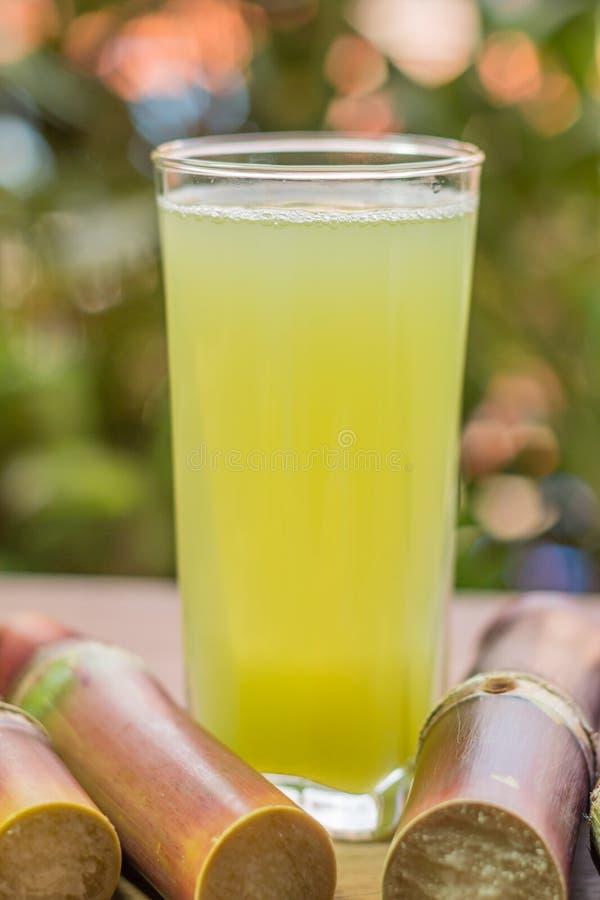 与甘蔗片断的甘蔗新鲜的汁在木backgrou的 库存照片