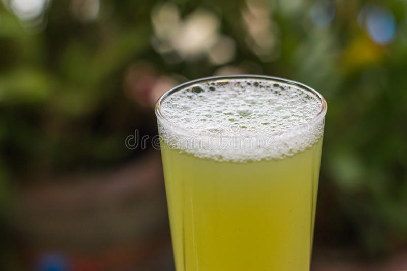 与甘蔗片断的甘蔗汁在木背景的 库存照片