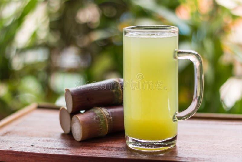与甘蔗片断的甘蔗汁在木背景的 免版税库存照片
