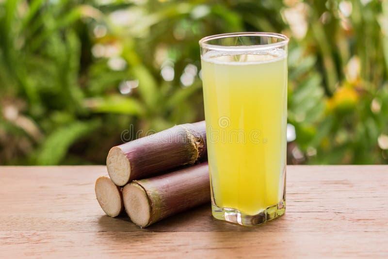 与甘蔗片断的甘蔗汁在木背景的 免版税图库摄影