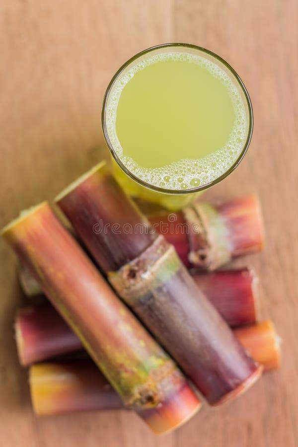 与甘蔗片断的甘蔗汁在木背景的  免版税库存图片