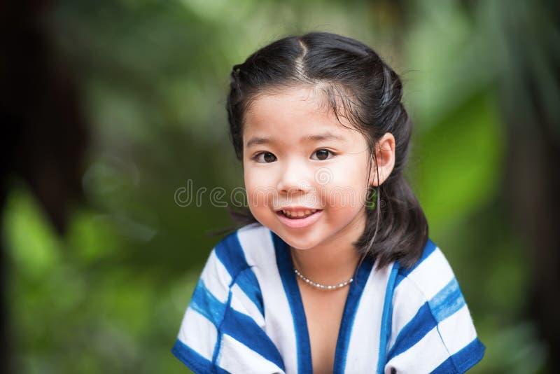与甜微笑面孔的一张逗人喜爱的亚洲女孩画象 库存图片