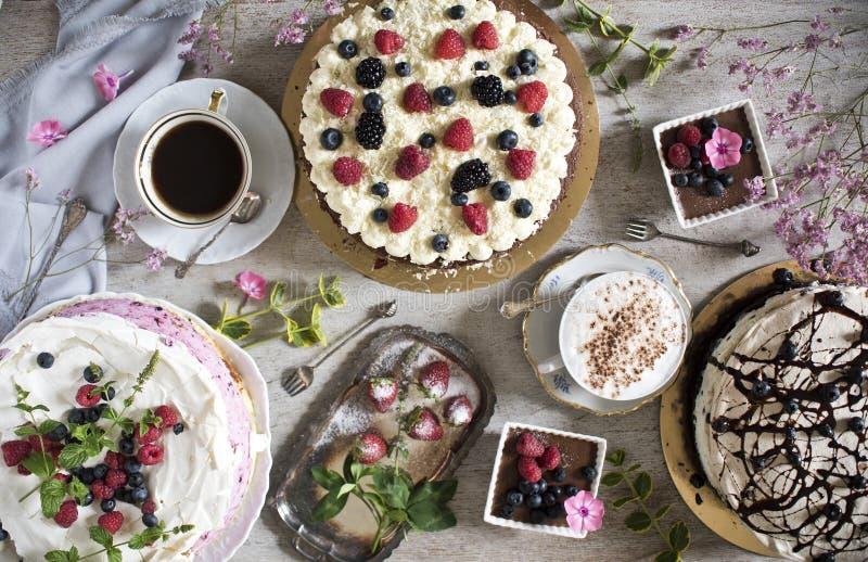 与甜点的一张桌和咖啡、葡萄酒匙子和叉子、花、草莓、蛋糕和点心 免版税库存照片