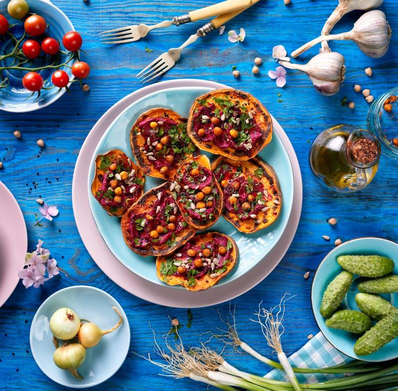与甜菜hummus、烤鸡豆、新鲜的荷兰芹、nigella种子和向日葵种子的白薯多士在蓝色ta的一块板材 免版税库存图片