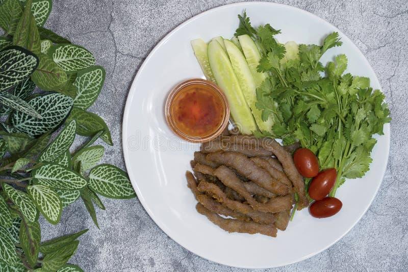 与甜辣味番茄酱和新鲜蔬菜盘的油煎的猪肉在c 免版税库存图片