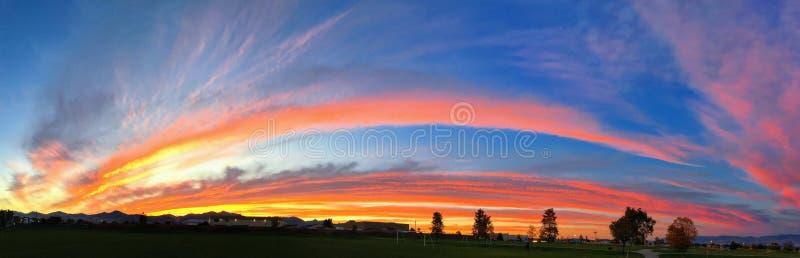 与生动橙色的全景醒目的日落背景,蓝色,红色和黄色,以彩虹的形式 免版税库存图片