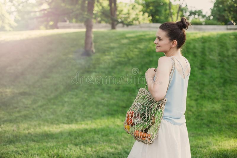 与生态零的废购物带来的年轻美女身分有菜的 免版税库存照片