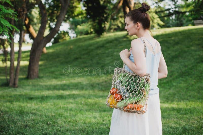与生态零的废购物带来的年轻美女身分有菜的 库存照片