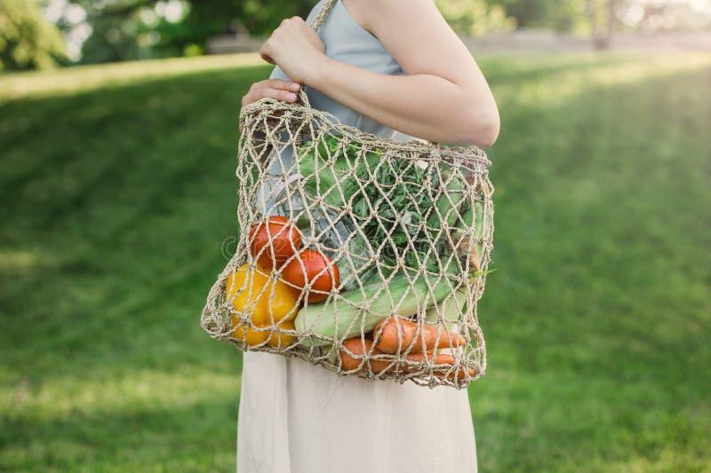 与生态零的废购物带来的年轻美女身分有菜的 库存图片