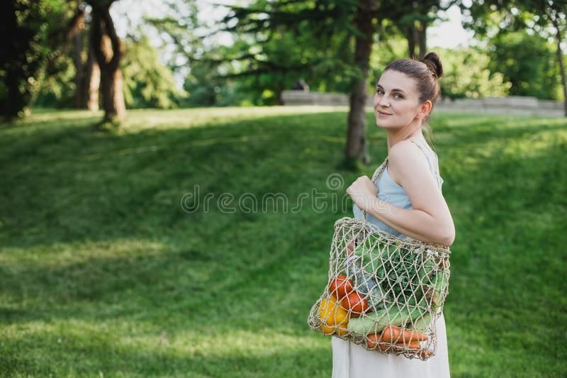 与生态零的废购物带来的年轻美女身分有菜的 免版税库存图片