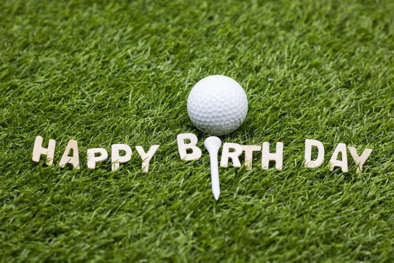 与生日快乐标志的高尔夫球在绿草 库存图片