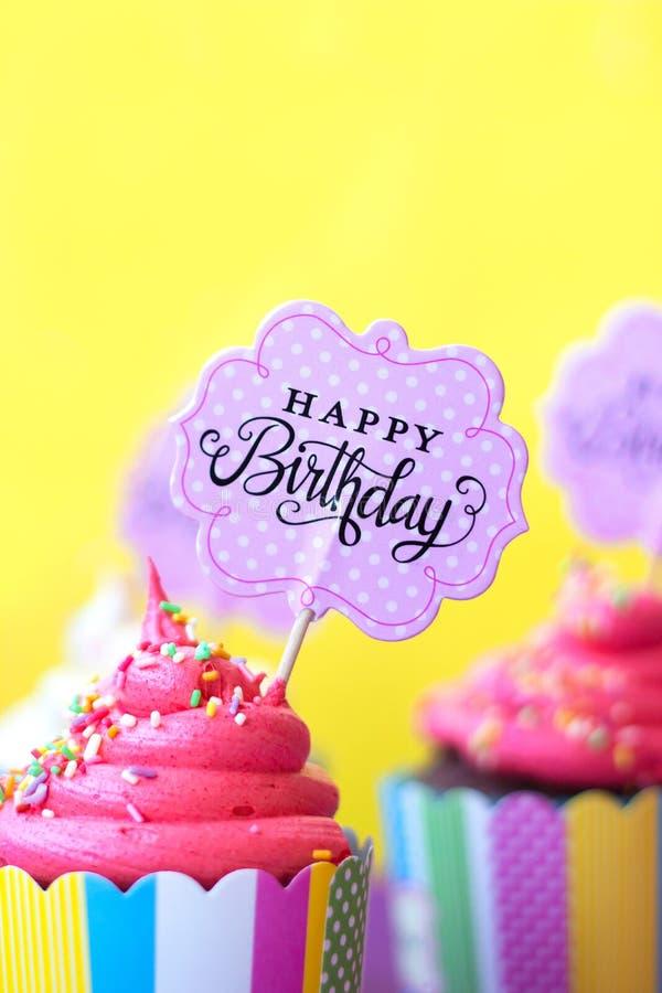 与生日快乐贺卡的鲜美草莓杯形蛋糕在y 免版税库存图片