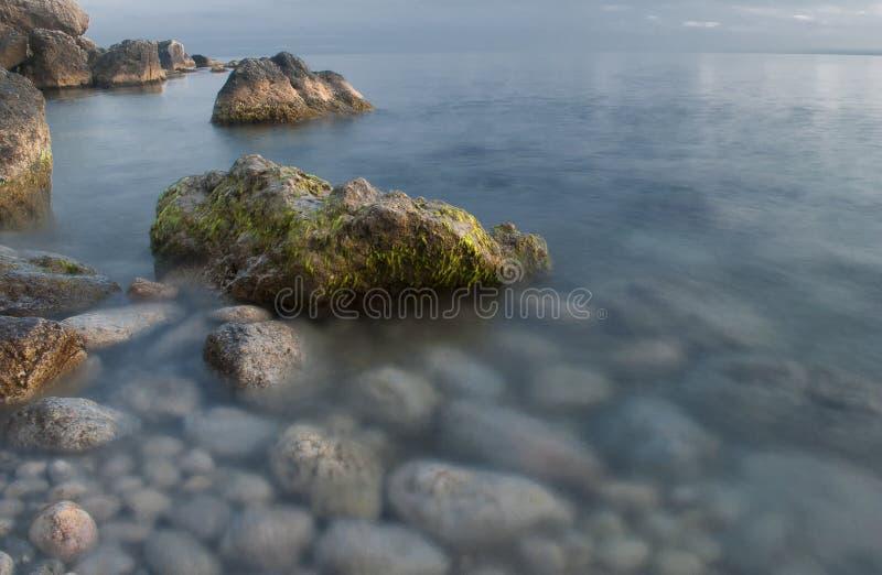 与生苔岩石的美丽的海滩 库存图片