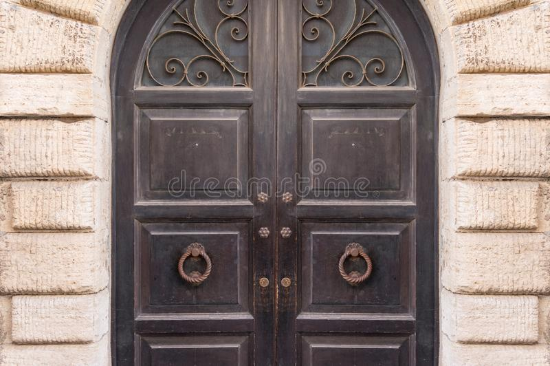 与生铁格子装饰,金属门把手的闭合的老牌木门 免版税图库摄影