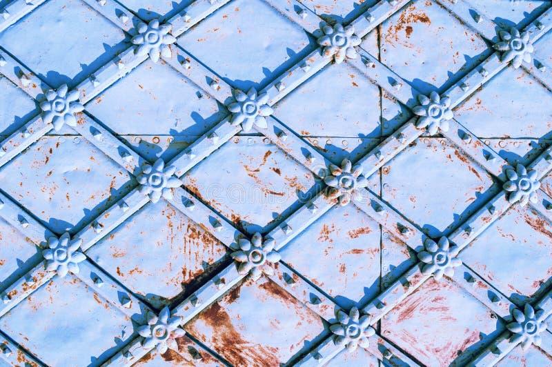 与生锈的建筑细节的葡萄酒金属浅兰的门以花的形式 金属建筑学背景 免版税库存图片