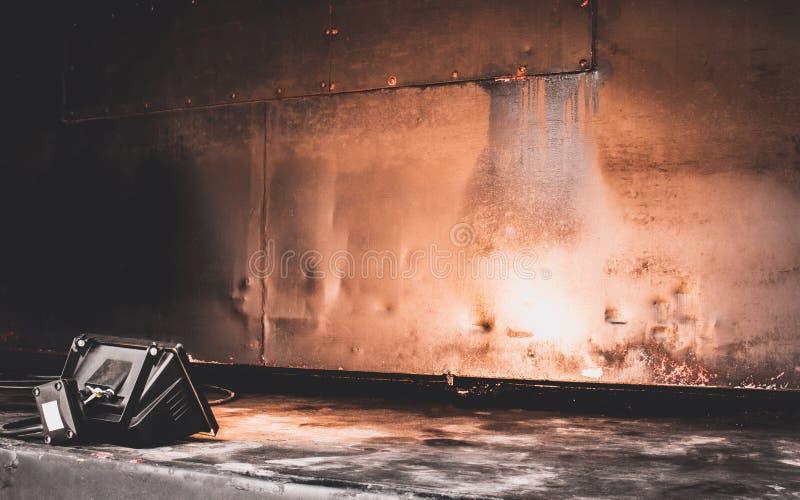与生锈的老被绘的金属墙壁纹理的演播室聚光灯  库存图片