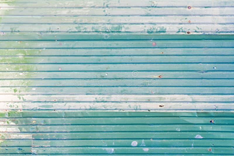 与生锈的表面的波纹状的被镀锌的钢绿色铁金属板纹理和背景的 免版税库存图片