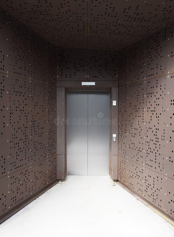 与生锈的金属未来派盘区的银色电梯门 免版税库存图片