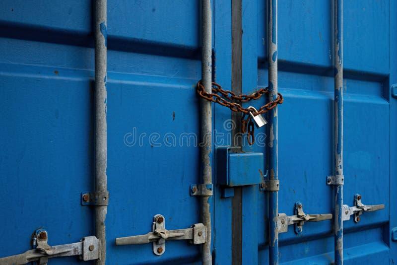 与生锈的链子和被锁的挂锁的蓝色容器门 免版税库存图片