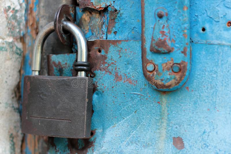 与生锈的锁和匙孔的老蓝色土气门 库存照片