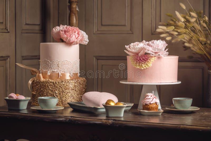 与用乳香树脂和玫瑰色金子装饰的一个美丽的桃红色蛋糕的豪华婚礼桌在古色古香的经典内部 库存照片