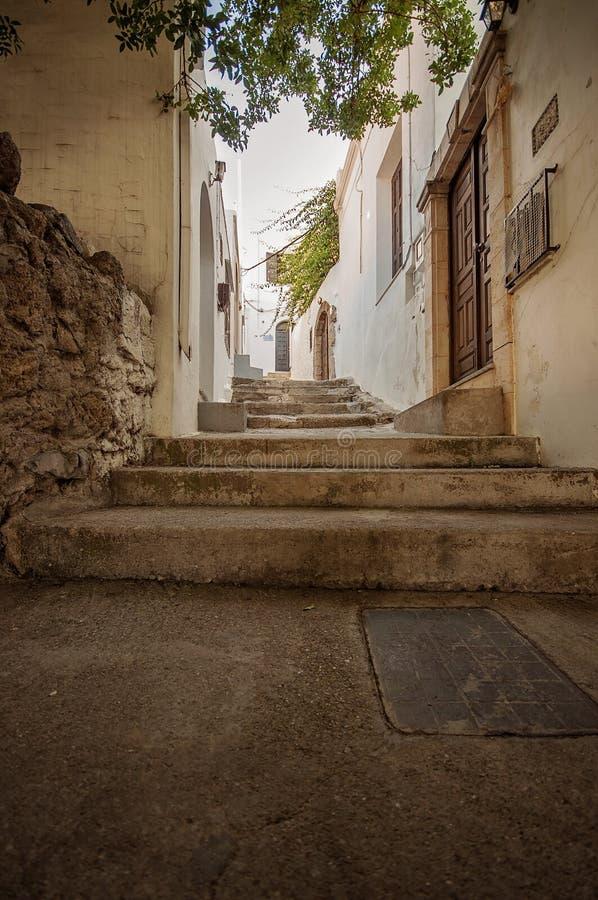 与用从希腊,罗得岛的藤盖的一个石墙的一个胡同楼梯视图 库存照片
