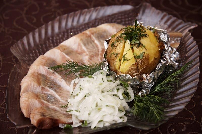 与用卤汁泡的鱼和葱的被烘烤的土豆 免版税库存照片