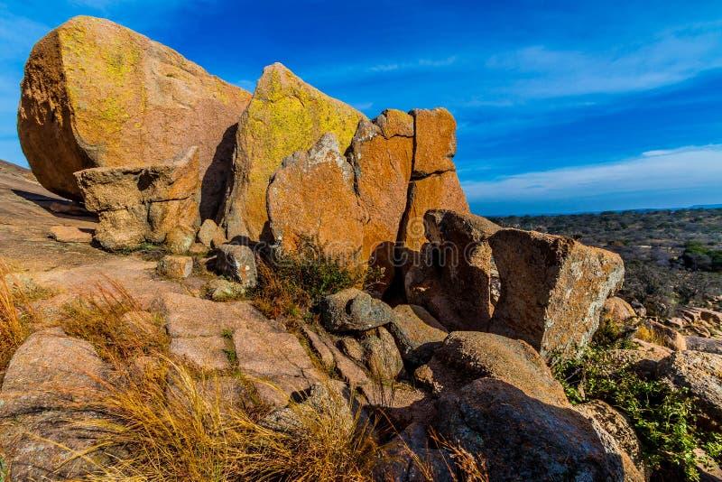 与用在着魔岩,得克萨斯的明亮地色的地衣盖的巨大的冰砾的一个美好的狂放的西部看法。 免版税图库摄影