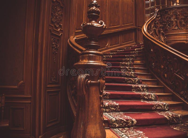 与用栏杆围的葡萄酒的老螺旋木楼梯户内,用地毯盖 豪华在宫殿雕刻了木内部 ?? 图库摄影