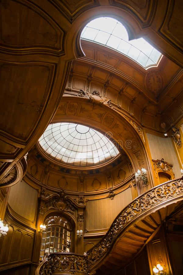 与用栏杆围的葡萄酒的老螺旋木楼梯户内 豪华在一个贵族宫殿的大厅里雕刻了木内部 ?? 库存照片