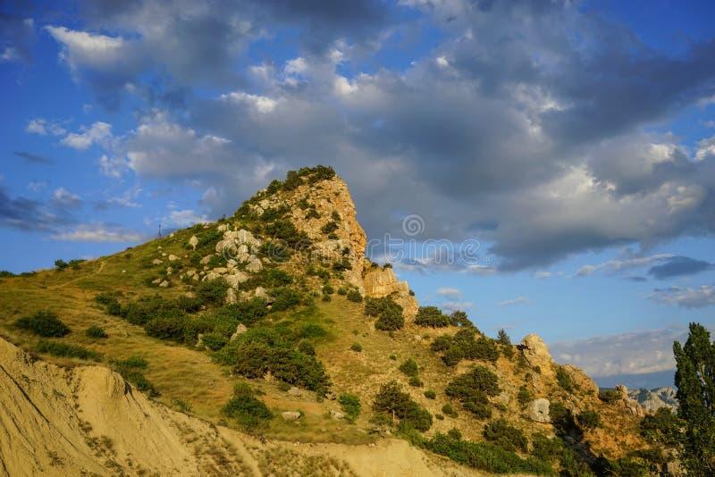 与用植被盖的高峭壁的自然风景在多云天空的背景中 免版税库存图片