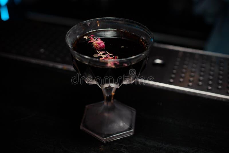 与用玫瑰花瓣装饰的酒精饮料的鸡尾酒杯 免版税库存图片