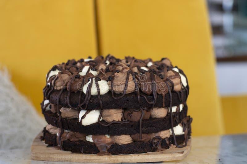 与用白色、牛奶和黑暗的巧克力沫丝淋填满的层数的巧克力沫丝淋蛋糕 免版税图库摄影