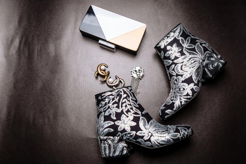 与用花装饰的厚实的脚跟的黑脚腕起动绣与银色衣服饰物之小金属片和一台金属传动器和别针在a 免版税库存照片